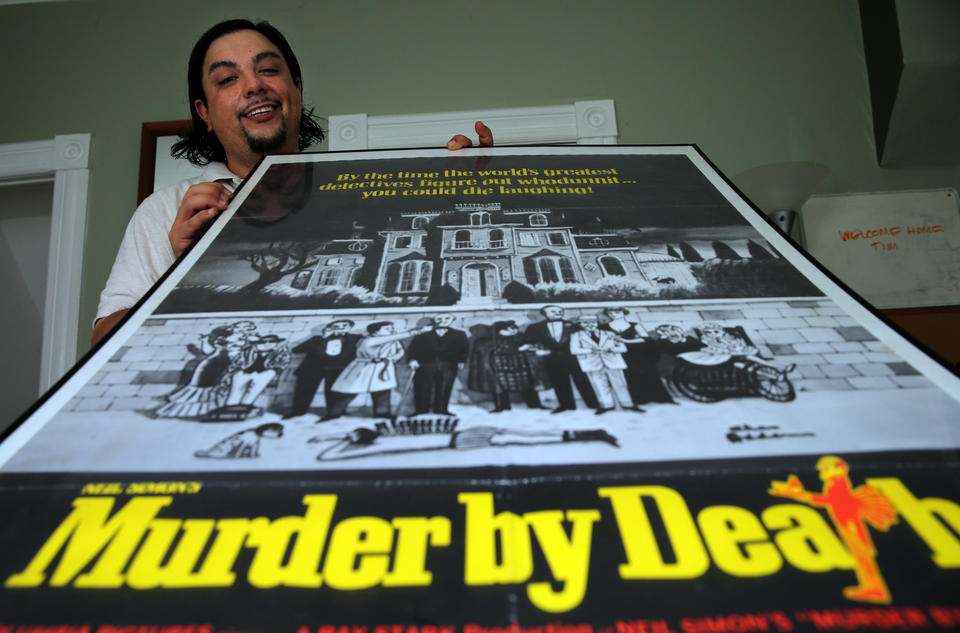 """Bill Cruz sits inside his Chicago home with a poster from the 1976 movie, """"Murder by Death,"""" one of his favorite comedies."""