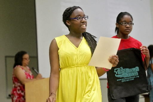 """Eurielle Langhorne, 12, center, and Nikiera Boothe, 13, right, smile after receiving a backpack during Wednesday's """"Yes! Dare 2 Dream"""" graduation celebration at Achievable Dream."""