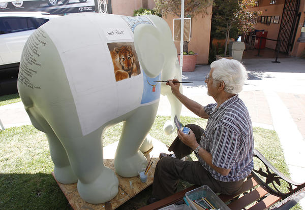 Artist Victor Dworak does his part to help conserve the world's majestic animals by adding a his touch to the baby elephant sculpture at Laguna's Art-A-Fair as part of the Elephant Parade Project on Wednesday.