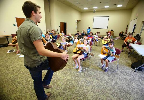 Classical guitarist Joshua Englert teaches free group guitar classes for ages 8 to 15 at the Cooper Memorial Library in Clermont, on Friday, July 19, 2013.