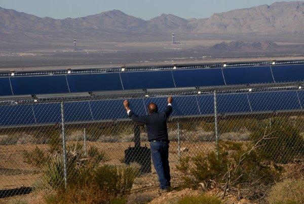 Ron Handley of Nipton, Calif., looks through the fence surrounding the Ivanpah solar thermal power plant.