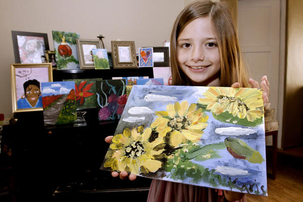 Artist Karis Zavala shows her top-10 finalist painting of sunflowers, at her home in Glendale on Wednesday, August 7, 2013. The eight-year old has been painting for two years and also was chosen as a winner in another competition.