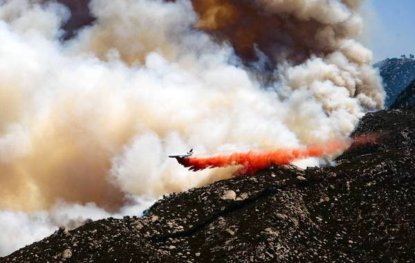 A plane drops fire retardant on the eastern flank of the Silver fire in Twin Pines, near Banning, on Thursday.