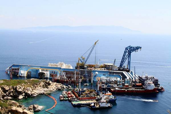 Equipment and workers surround the capsized cruise ship Costa Concordia off the coast of the Italian island of Giglio. Crews are racing to right the ship in September, before winter storms arrive, so it can eventually be towed away.