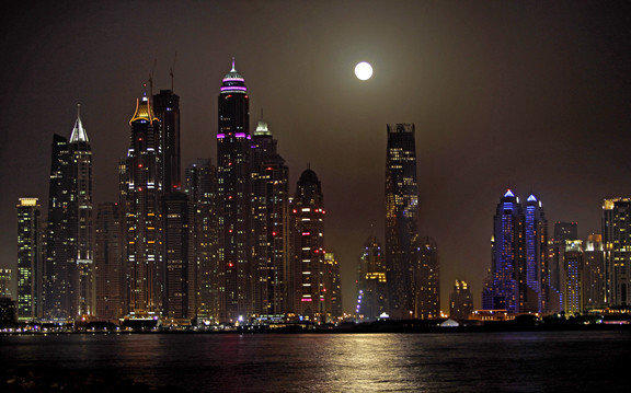 The full moon is seen behind the Marina district towers in Dubai.
