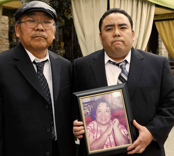 Peter Uno, left, with his son Jeffrey Uno holds a photo of Noriko Uno, who died in the crash of a Toyota Camry. Their suit claims Toyota failed to install a safety device that would have prevented the crash.