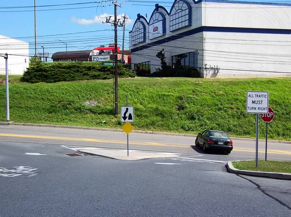 A motorist turns left to exit the Rite-Aid pharmacy lot on Mickley Road in Whitehall Township, despite the sign and the path laid out by the concrete island.