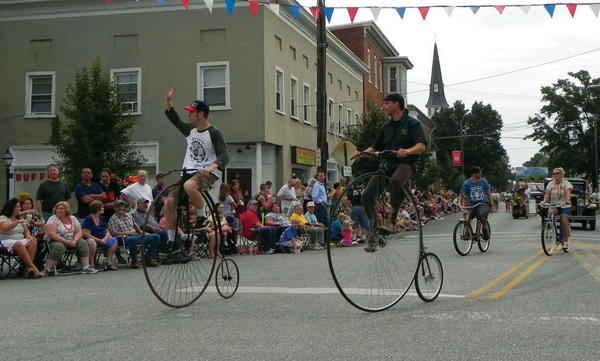 Two Old Home Week parade participants greet crowds in the town square from atop their penny-farthing, high-wheel bicycles.