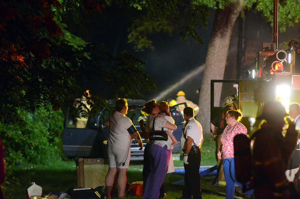 A couple stand with their baby boy on July 29 as their Hanover Township, Lehigh County, home goes up in flames along the Lehigh River. Firefighters battled the blaze at 2080 N. Dauphin St. for more than an hour before bringing it under control.