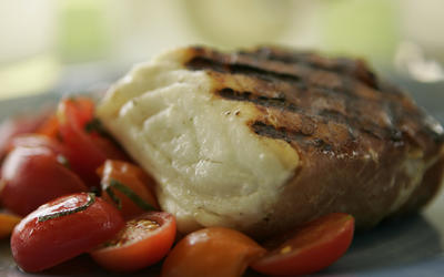 Prosciutto-wrapped halibut with grape tomato salad
