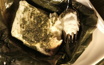 Grilled halibut with cilantro-lime sauce in banana leaves