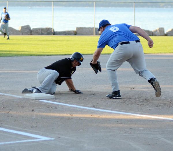Adam Dustin Memorial third baseman Jason Peters (right) attempts to tag Bay Street Orthopaedics Kevin Thompson during a Petoskey Mens Softball League game Thursday at Bayfront Parks Ed White Field. Bay Street defeated Dustin Memorial, 12-6.