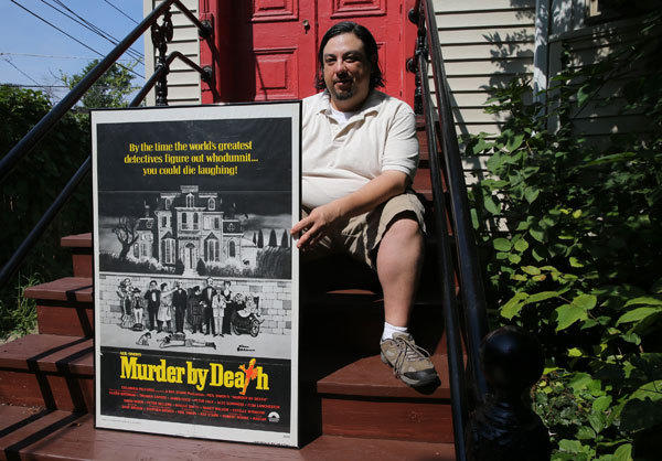 Bill Cruz sits outside his Chicago home with a poster from the 1976 movie, Murder by Death, one of his favorite comedies. Cruz will be hosting a screening of the movie at Facets midnight Saturday.