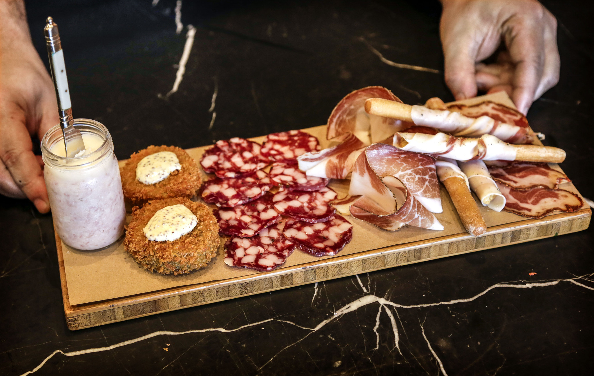 The Affettati Misti plate just prepared by Chef Chad Colby at CHI SPACCA. Featured on the plate from left to right is Pork butter, Trotter Fritti, Trappist Salami, Joe's Tocai Salami, Speck, Lardo wrapped grissini and Capocollo. (Ricardo DeAratanha/Los Angeles Times).