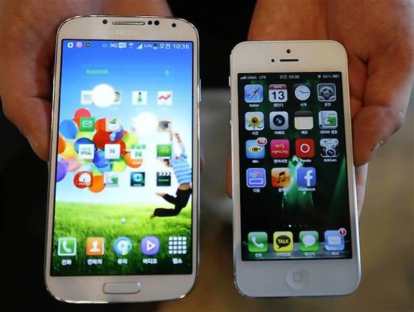 An employee of a smartphone store shows Samsung Electronics' Galaxy S4 and Apple's iPhone 5 taken in Seoul.
