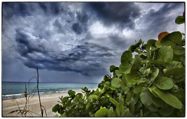 Storm clouds over a deserted Indialantic Beach, Fla., create a textured, foreboding scene, Sunday, August 4, 2013. (Joe Burbank/Orlando Sentinel) .