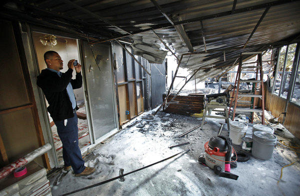 Will Mata, working for ServiceMaster contractors, takes photos of the fire damage to a home in North Hills, which is next door to the destroyed single-story home where firefighters found the bodies of a man and a dog as they were fighting the raging blaze.
