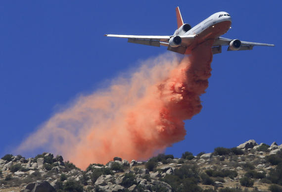 A DC-10 tanker drops retardant ahead of the fire line on the mountains above Snow Creek Village near Cabazon as the 16,000-acre Silver fire in Riverside County continues to burn.