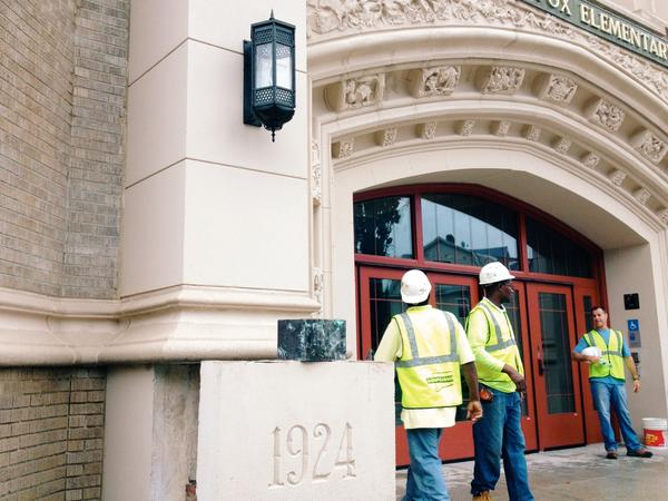 Employees with Connecticut Mason Contractors stand outside the renovated M.D. Fox School, the original home of Bulkeley High, after removing a 1924 time capsule that was hidden behind the cornerstone during the first year of Bulkeley's construction.