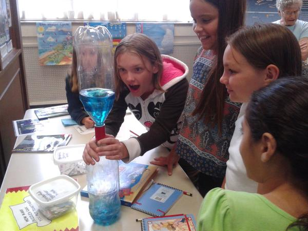 Sydney Lee, left, of Rockville stares at a simulated tornado made from the liquid in the two bottles she is holding taped together at the Amazing Science Camp at Discovery Station with her sister Faith Lee, right, and Kylee McKenrick of Hagerstown, center. Ava Selby of Boonsboro, far left, and Camilla Montoya, far right, of Boonsboro also look on.