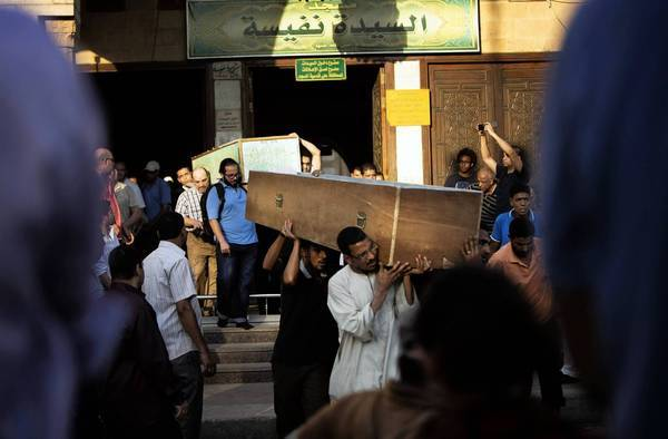 Men in Cairo carry the coffins of Shiite Muslims slain in a mob attack in the nearby village of Abu Mussalem in June. Then-President Mohamed Morsi condemned the attack but, in a pointed omission, did not specify that the victims were Shiites.