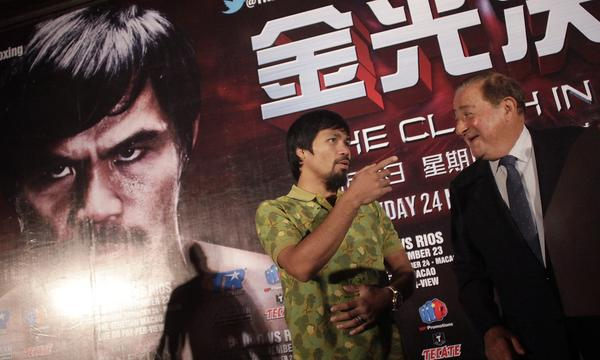 Promoter Bob Arum, right, speaks with boxer Manny Pacquiao before a news conference in Shanghai, China, on July 31. Arum may be in his eighties, but he's still taking risks.