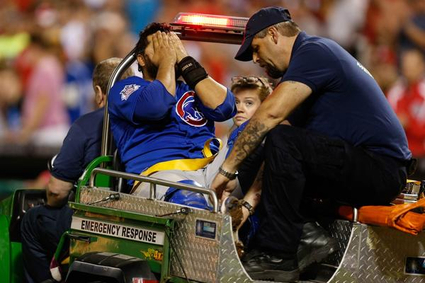 Cubs catcher Dioner Navarro holds his hands over his face as he rides in a medical gator off of the field after colliding with Chase Utley at the plate in the seventh inning.