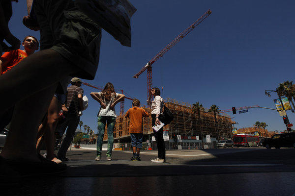 Anja Heimann and her fiance's children Ben Heidenreich, 9, and Emily Heidenreich, 13, wait to cross the road near where construction takes place at the intersection of Hollywood and Argyle in Los Angeles.