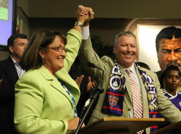 Orange County Mayor Teresa Jacobs and Orlando Mayor Buddy Dyer hold their hands high Friday, August 9, 2013 after the Tourist Development Council approved a $94.5 million package that could bring Major League Soccer to the region.