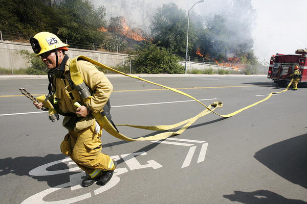 A Glendale firefighter drags hose along Harvey Avenue to battle a brush fire that erupted in the Glenoaks and Chevy Chase canyons in Glendale on Friday, May 3, 2013. More than 1,600 people applied to fill 15 new Glendale firefighter positions.
