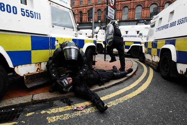 A police officer is tended to by a colleague after Loyalist protesters attacked the police with bricks and bottles as they waited for a republican parade to make its way through Belfast.