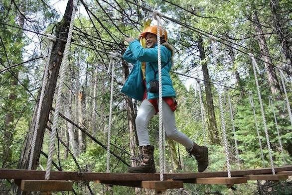 A participant crosses some of the tree-top bridges during a daylight zipline tour at Zip Yosemite in Oakhurst, Calif.