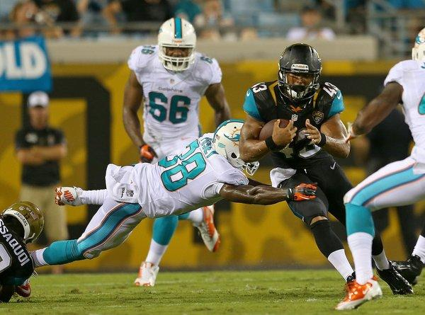 Marcus Burley #43 of the Jacksonville Jaguars rushes past Julian Posey #38 of the Miami Dolphins during a preseason game at EverBank Field on August 9, 2013 in Jacksonville, Florida.