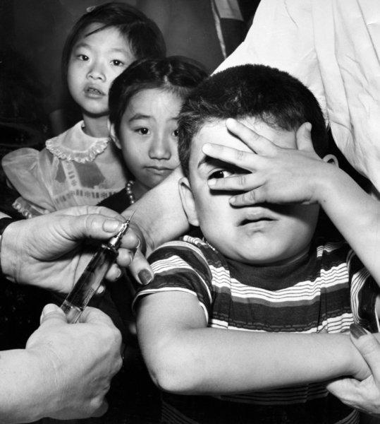 A 7-year-old and his classmates await polio vaccinations at Castelar Street Elementary School in Los Angeles in 1957.