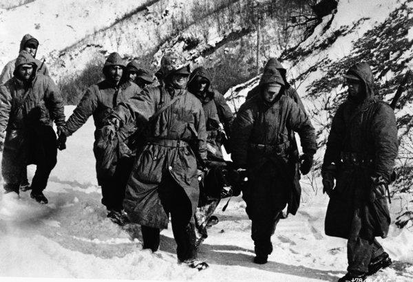 "A frostbite victim is carried from the front lines as U.S. Marines and soldiers battled bitter cold as well as the enemy during their ""fighting withdrawal"" from the Chosin Reservoir during the Korean War."