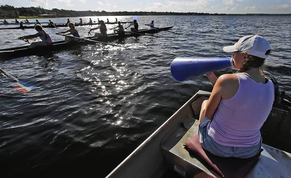 "Chelsea Curto, 23, right, with Orlando Area Rowing Society coaches novice rowers during a summer camp on Lake Down in Windermere, Florida. Surging interest in Central florida rowing. Rowing enthusiasts are trying to propel the growing sport in Lake County. For about a year, the Lake County Rowing Association has been recruiting more high-schoolers and families, holding ""Learn to Row"" events on Lake Minneola, where Clermont officials now want to build a rowing complex, expected to cost about $750,000. (Red Huber/Staff Photographer)"