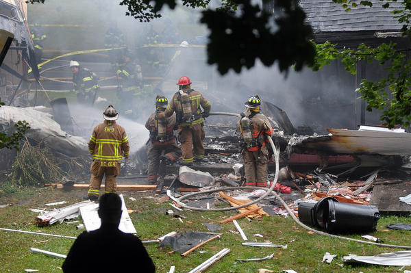First responders work the scene in East Haven, Conn., where a plane crashed into a residential neighborhood a few blocks from an airport. Four people died, including two children in a house set on fire.