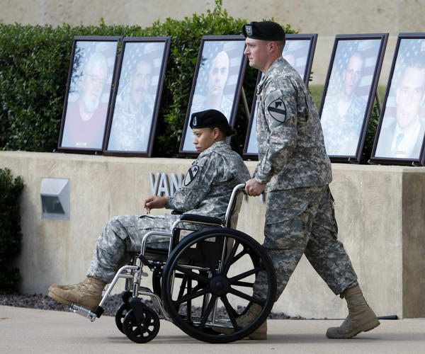 An injured soldier is wheeled past pictures of slain soldiers and a civilian whom U.S. Army Maj. Nidal Hasan has admitted to killing at Fort Hood in 2009. (Reuters)