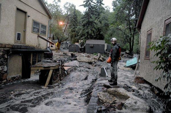 Volunteer rescuer Jesse Rochette searches the Fountain Creek flood waters for anyone trapped or stranded as another flash flood washes off the Waldo Canyon burn scar in Manitou, Colo.