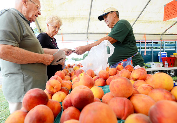 C.M. Miller, left, and Dorma Jones of Luray Va., buy peaches from Ivy Hill Farm volunteer Larry Cassell Saturday afternoon at the annual Leitersburg Peach Festival.