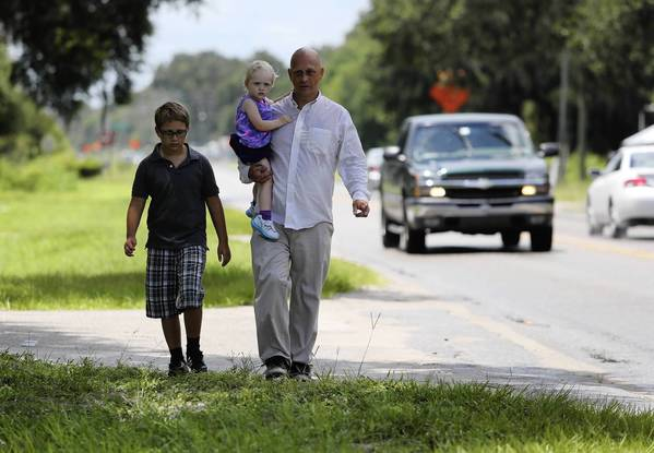 Scott Larson and his son Nathan walk part of the route that Nathan, a third grader, will have to take to school. Busing cutbacks approved by Lake County School Board members have parents furious and confused over how their children will get to school when classes begin in less than two weeks. More than 4,000 children won't be getting courtesy bus service meaning more children may be hoofing it to class down dangerous walkways. (Tom Benitez/Orlando Sentinel)