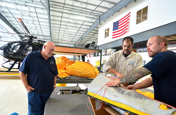From left, Darrell Condry, chief inspector at Mecaer Aviation Group Inc. (MAG, Inc.), Andrew Lewis, director of Maintenance and technician Donald Wright work on packing emergency floats for an Agusta Westland 139 helicopter at the Hagerstown facility Wednesday.