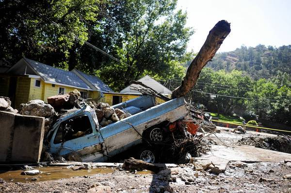 A truck is left crushing a car after a flash flood in Manitou Springs, Colo. Rescuers were combing roads and mountainsides in search of two missing men and one woman.