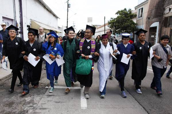 "The ""Dream 9,"" eight of them wearing graduation caps and gowns to show their desire to finish school in the U.S., march to a U.S. port of entry last month."