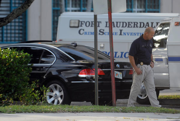 Fort Lauderdale Police work the scene at a side entrance to Broward Sheriff's headquarters on NW 27th Ave., just north of Broward Blvd., where a man was found shot dead in the black BMW.