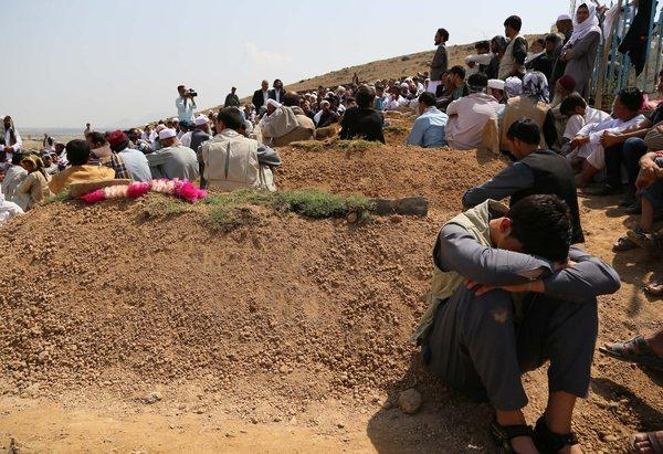 Afghans affected by floods bury the victims in the Shomali plains on the outskirts of Kabul on Sunday. Heavy floods left at least 22 people dead, officials said.