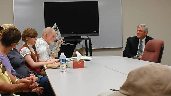 Leonard Wheeler, an advocate for the disabled, holds a front-page story from the Orlando Sentinel about pedestrian deaths while discussing traffic safety with U.S. Rep. Dan Webster, R-Winter Garden, in Eustis. Wheeler is advocating for building sidewalks where officials failed to build them. Seated next to Wheeler is Stephanie Leason, a 26-year-old blind woman.