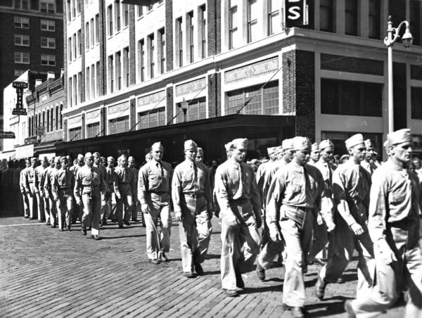 Soldiers march on Orlando's Orange Avenue during a July 4 parade in the World War II years, probably 1943 (the building behind them at Orange and Central Boulevard then housed the Dickson & Ives department store). On Aug. 14, 1945, a much less orderly crowd filled downtown streets to sing and cheer the end of the war.