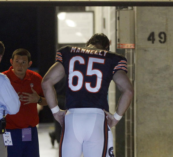 Bears long snapper Patrick Mannelly walks in the tunnel after being injured in the first quarter Friday.