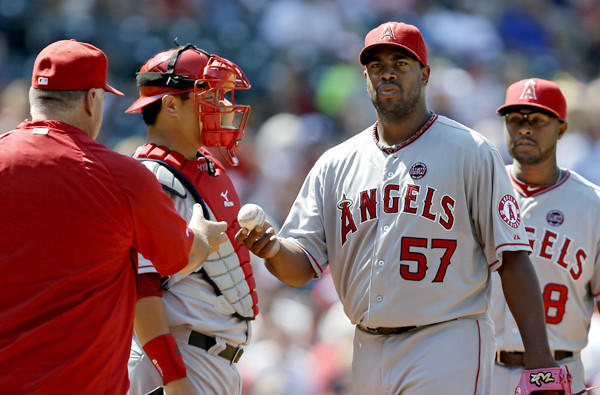 Angels starting pitcher Jerome Williams hands the ball to Manager Mike Scioscia after getting knocked out of the game in the sixth inning against the Indians on Sunday in Cleveland.